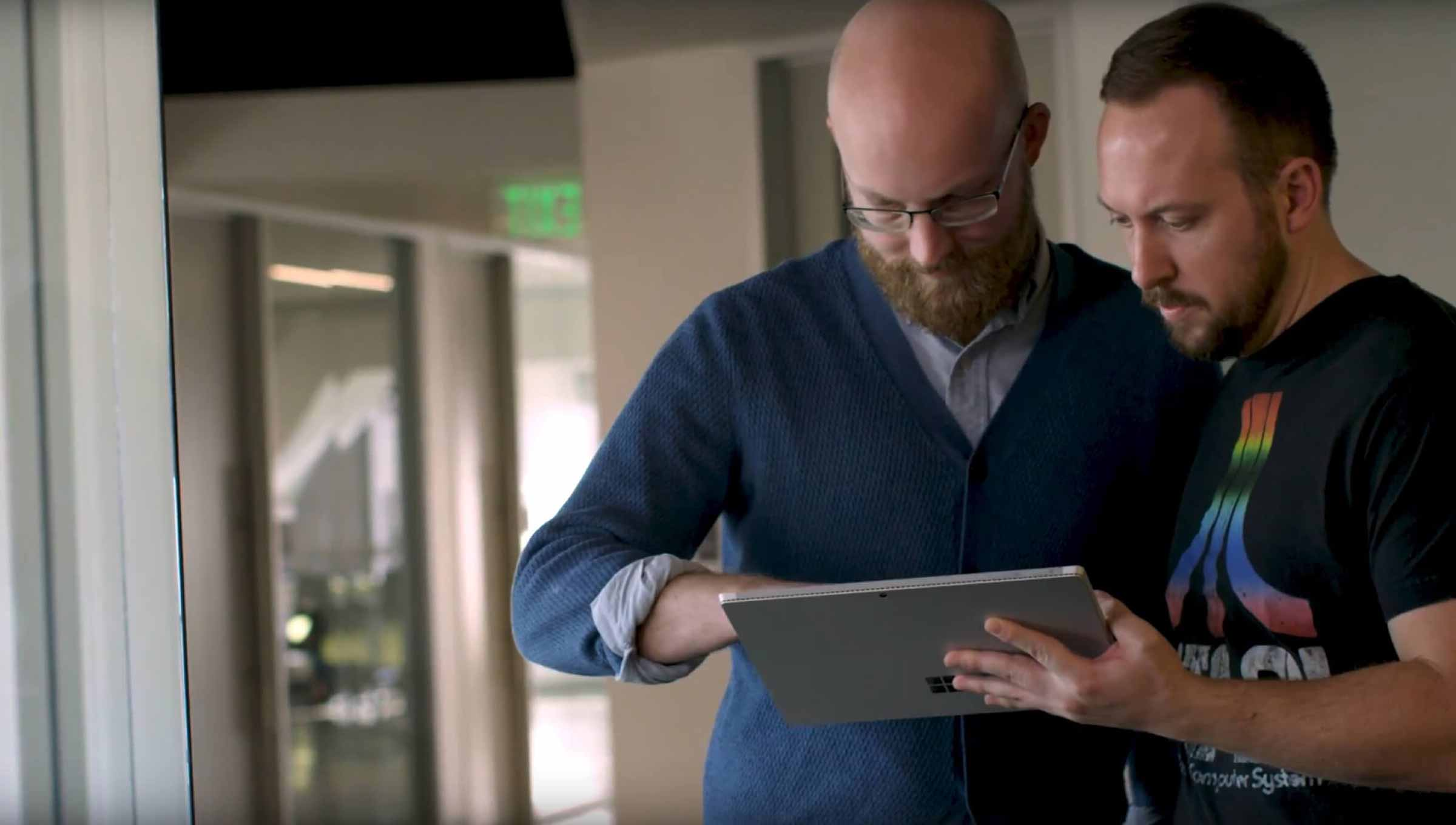Two men looking at a Microsoft surface in an office hallway.
