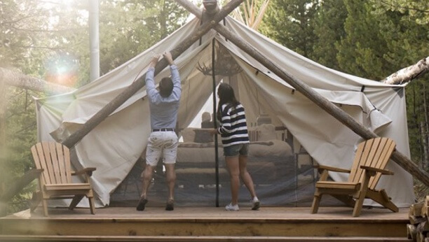 Two people constructing a luxurious tent.