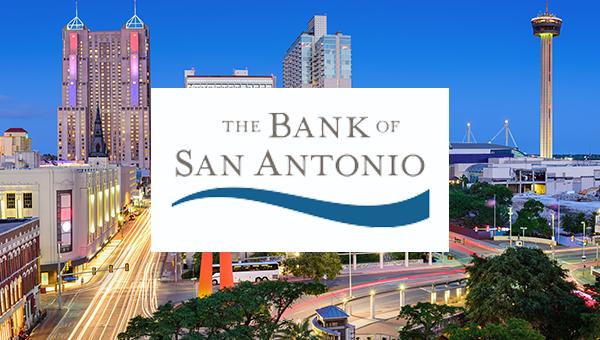 The Bank of San Antonio Logo over the San Antonio skyline at night.