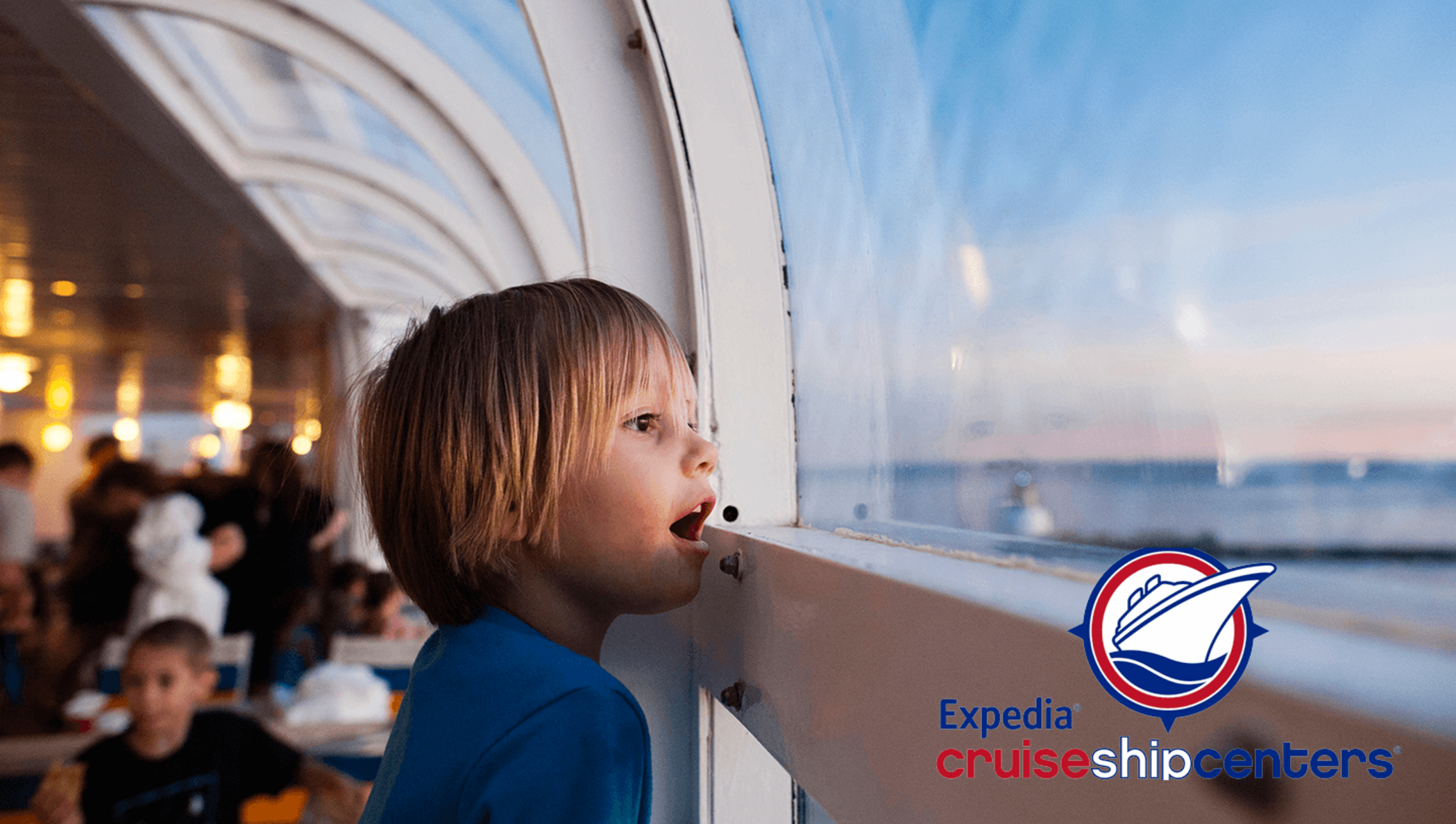 A little boy looking out a cruise ship window in awe at the landscape, mouth agape.